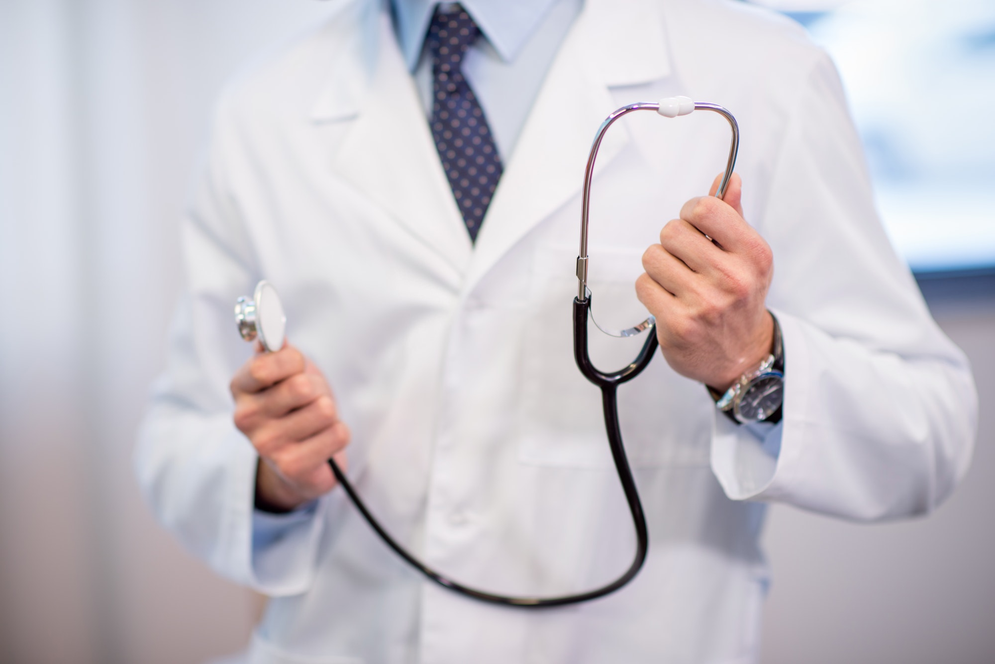 Close-up partial view of male doctor holding stethoscope